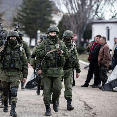 Taisteluvarustuksessa olevat, venäläisiksi epäillyt sotilaat marssivat Simferopolissa Krimillä vuonna 2014.