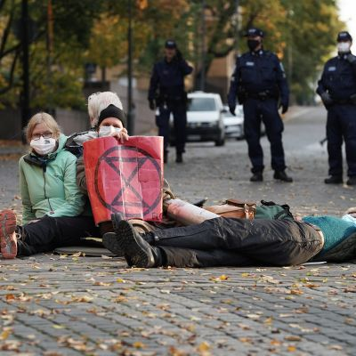 Mielenosoittajia istumassa kadulla