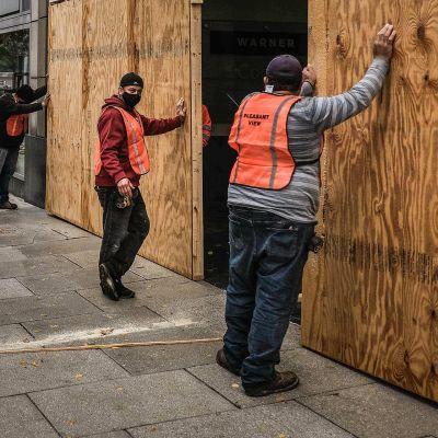 Työmiehet suojaavat puulevyillä kaupan ikkunoita mellakoiden varalta Washingtonissa.