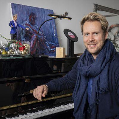 Oopperalaulaja Waltteri Torikka istuu pianon äärellä.