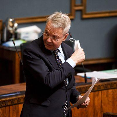 Ulkoministeri Pekka Haavisto riisuu kasvomaskin ennen puhumistaan eduskunnan täysistunnossa 30. marraskuuta.