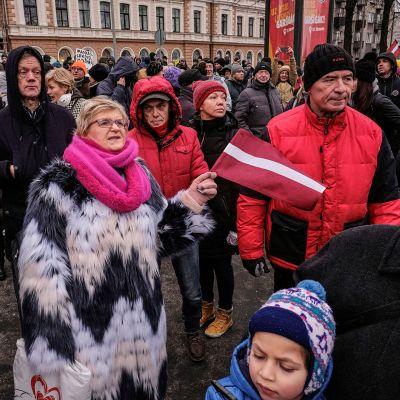 Mielenosoittajia Riikassa osoittamassa mieltää koronarajoituksia vastaan.
