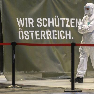 Suojavarusteisiin pukeutunut mies testausasemalla Wienissä.