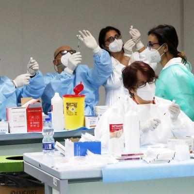 Suojapukuiset henkilöt annostelevat rokotteita ruiskuihin.