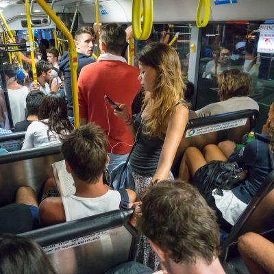 Bussissa matkustajia tutkien puhelinta.