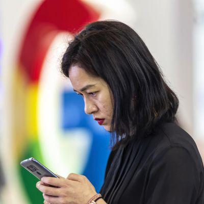 Nainen selaa puhelinta Googlen logon edustalla messuilla Guiyangissa Kiinassa