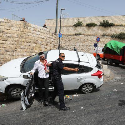 Israelilaine npoliisi osoittaa aseella palestiinalaismiestä.