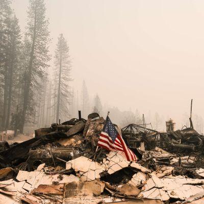 Yhdysvaltain lippu seisoo keskellä talon raunioita maastopalon jäljiltä.