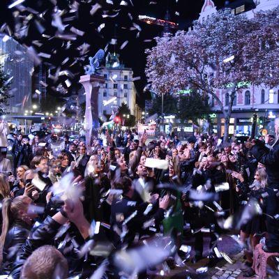 Ihmisjoukko heittelee paperilappuja ilmaan