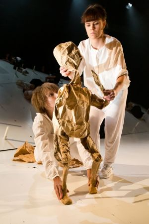 ur kalevalaproduktionen på ÅST: två vitklädda kvinnor håller i en brun dockfigur