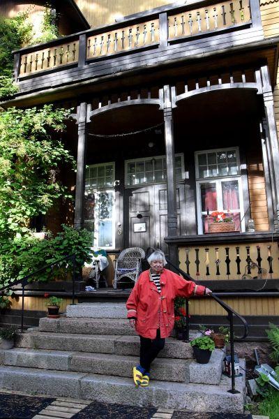 kvinna i röd jacka på trappan till hus