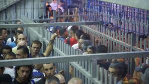Palestinska män köar i checkpoint Tarqumia
