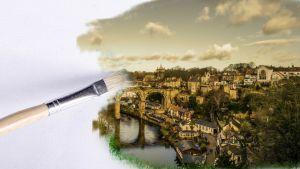 keskeneräinen maalaus kaupungista ja pensseli