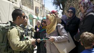 Lärare protesterar mot att israeliska soldater vägrar släppa dem förbi vägspärren
