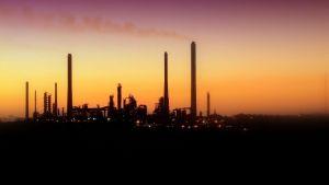 Tiotals fabrikspipor i vacker solnedgång med dis i luften