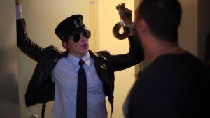 Kvinna står i dörröppningen i poliskostym och viftar med handklovar