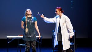 En person siktar på en annan person med pistol i en teaterpjäs.