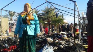 Flyktingkvinna intill ett utbrunnet tält i flyktinglägret Takiya i Irak i december 2015