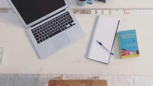 Nora Rosendahls laptop och anteckningsblock och kaffekopp.
