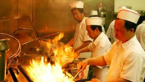 Kinesiska kockar wokar under hög värme.