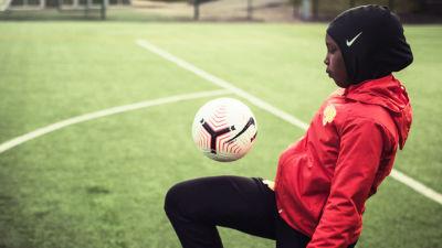 Jalkapalloa pelaava tyttö.