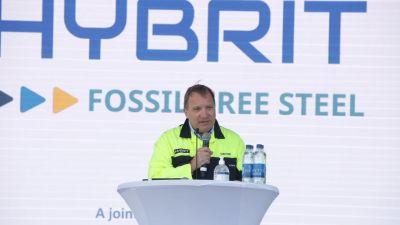 Stefan Löfven i industriskyddsjacka talar vid ett podium vid stålverket.