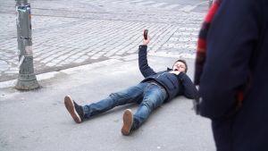 joakim rundt ligger på trottoaren invid en lyktstolpe och fotograferar med sin smarttelefon
