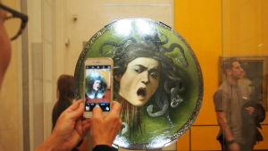 En man fotografer ett konstverk med mobilen på konstmuseet Uffizierna i Florens.