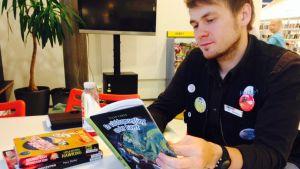 Bibliotekarien Mikael Gros bläddrar i barnböcker