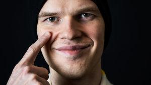 Kuvassa mieshenkilö, joka osoittaa sormella kohti silmää.