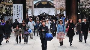 Folkvimmel i Tokyo, med det japanska kejserliga vapnet i bakgrunden.
