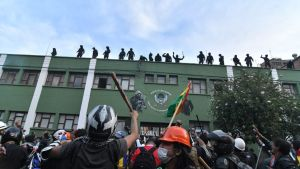 Joukko presidentti Moralesia vastustavia poliiseja vilkutti perjantaina mielenosoittajille poliisiaseman katolla Cochabambassa.