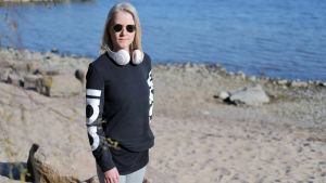 Kvinna med blong page och svarta solglasögon står vid en strand en solig vår dag.