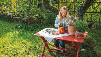 Alexandra de Paoli sitter och pysslar med örter vid ett trädgårdsbord. Gården är somrigt grönskande.