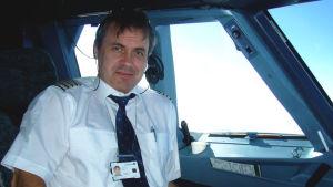 En medelålders manlig flygpilot sitter i ett flygplan och tittar mot kameran