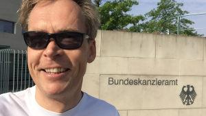 Kaj Arnö ler utanför en statsbyggnad i München