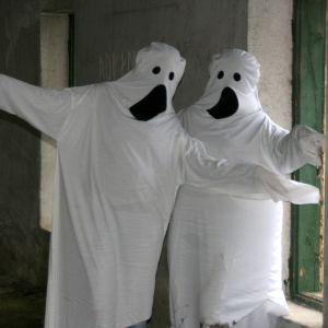 Två människor utklädda till spöken (med hjälp av vita lakan).