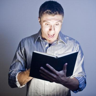 Man blir ivrig över något han läser i en bok.