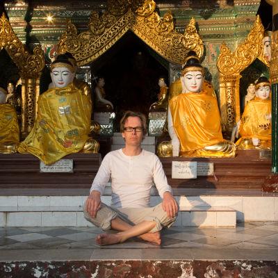 Kaj Arnö sitter framför buddhastatyer