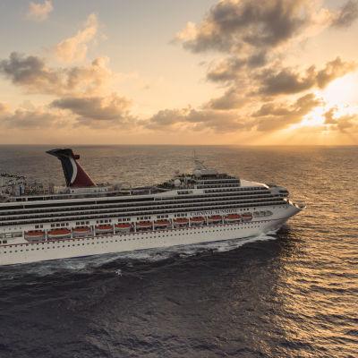 Ett stort kryssningsfartyg kryssar på havet i solnedgången.