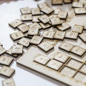 Det periodiska systemet i trä, alla ämnen ligger huller om buller på ett bord.