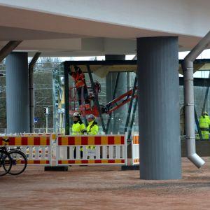 Nägra byggnadsarbetare arbetar vid en glasinhägnad under en bro.