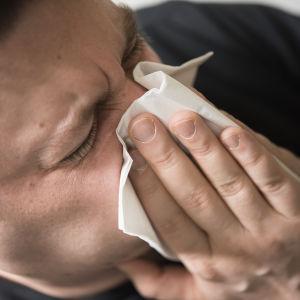 man som snyter sig i en näsduk.