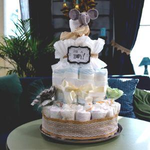 En tårta gjord av engångsblöjor dekorerad med virkade spetsar, pappersblommor och en babyleksak. Blöjtårtan används som dekoration på en baby shower.