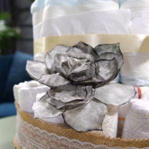 En grå handgjord pappersros tillverkad av färgat kaffefilter.