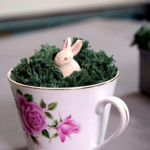 En kaffekopp med grönt garn och en kanin i garngräset