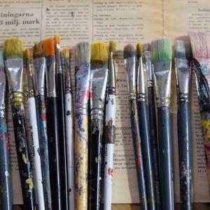 Ett dussin använda konstnärspenslar.