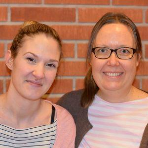 Två damer, en tegelvägg i bakgrunden.