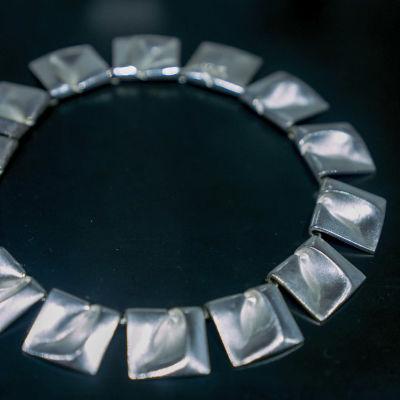 Ett stort halsband i silver med svart bakgrund.