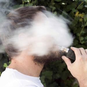 Person som röker e-cigarrett.